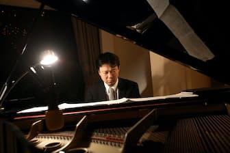 ピアノを弾くシティグループ証券の資本市場本部長、藤川大策氏