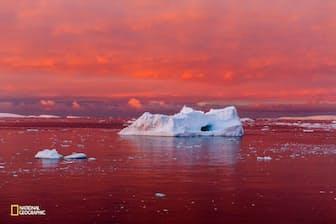 沈みゆく太陽が、南極半島の西岸沖に位置するルメール海峡を赤く染める。南極大陸を取り巻く海や大気の温暖化が進むにつれ、沿岸部の氷は崩れてきている。(Camille Seaman/National Geographic)