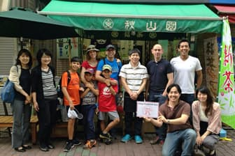 外国人観光客に東京都江東区の砂町銀座商店街を案内するノットワールドの佐々木文人社長(前列左、画像は一部加工してある)