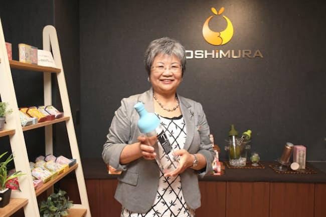 橋本久美子社長と、水出し日本茶が手軽につくれるワインボトル型の茶器。ユニークな独自商品は社員の自由な発想から生まれる (写真:都築雅人)
