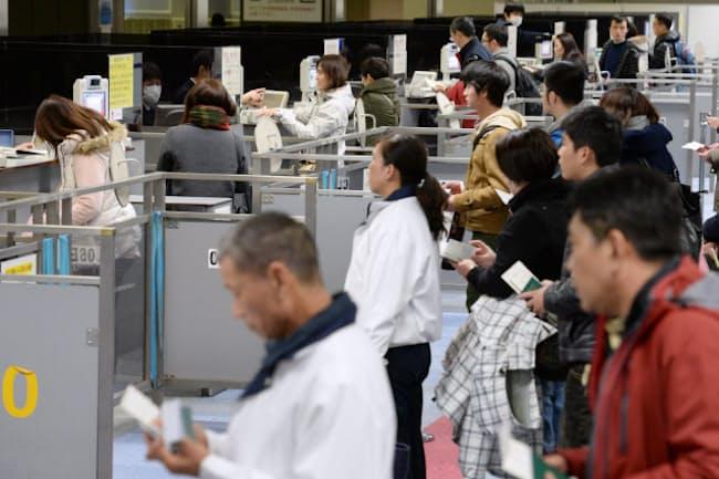成田空港で入国審査を受ける外国人観光客ら
