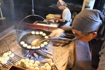 囲炉裏にかけた焙烙で焦げ目をつける小川の庄縄文おやき村(小川村)の縄文おやき。奥では具材を入れている