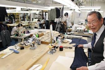 英国屋の本社工房では最高技術者の水本忠正氏(右)をはじめ、約40人のスーツ職人が働く(東京都中央区)