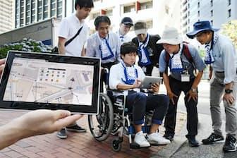 車いす体験をしながらタブレット端末でバリアフリーマップを作成する参加者ら(7月14日、東京都千代田区)