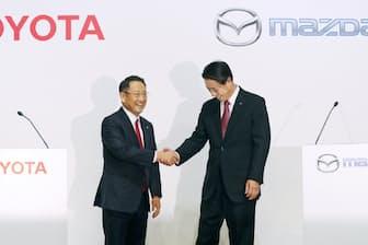 記者会見で握手するトヨタ自動車の豊田社長(左)とマツダの小飼社長(4日午後、東京都中央区)