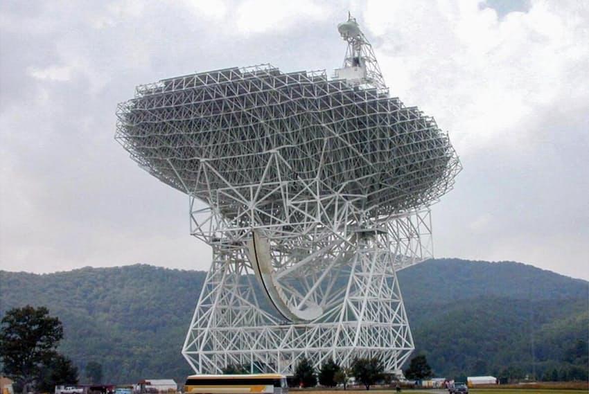 米国ウェストバージニア州にある超高感度の電波観測所、グリーンバンク望遠鏡。駐車しているバスと比較すると、その大きさが実感できる。(PHOTOGRAPH BY NRAO/AUI, REUTERS)