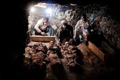王家に仕える金細工職人の墓から出土したミイラを調べる考古学者たち。2017年9月9日、エジプト、ルクソールにある古代エジプト新王国時代の墓で。(PHOTOGRAPH BY NARIMAN EL-MOFTY, ASSOCIATED PRESS)