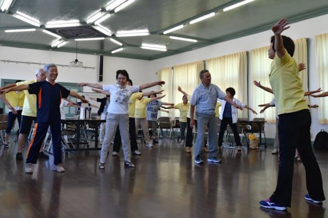 歌いながら体を大きく動かし、足腰を鍛える参加者たち(8月、長野県須坂市)