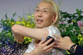 上腕部に着けたセンサー(白いボタン状のもの)に読み取り装置を近づけてグルコース値を測る假屋崎さん