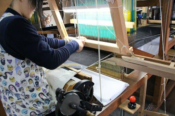 クスカのネクタイは、木製の機織り機で生地を織る(京都府与謝野町)