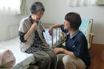 酸素吸入のケアを受ける「看多機」の利用者(左)(神奈川県横須賀市)