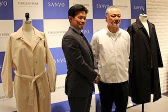 新しいコートを発表する岩田功社長(左)と、デザイナーの森下公則氏(2017年5月25日、東京都中央区)