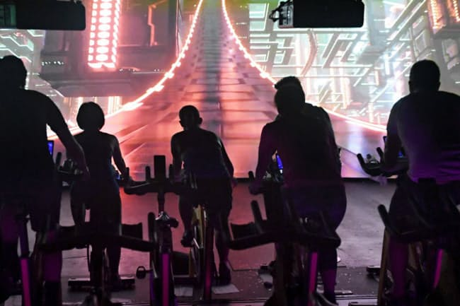 映像を見ながら、音楽に合わせて自転車型の運動器具をこぐ「ザ・トリップ」の参加者(東京都渋谷区の「サイクル&スタジオR渋谷」)
