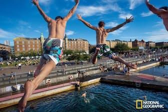 コペンハーゲンの港にある高さ5メートルの飛び込み台から、若者たちがジャンプ。気軽に運動できる設備が随所にあるデンマークは、肥満率が世界最低レベル。世界幸福度ランキングでもたびたび1位になる。(Cory Richards/National Geographic)