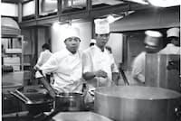 1964年の東京五輪で厨房に立つ大和丈司さん(右)