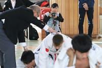 視覚障害者柔道の大会を取材する法政大の伊藤さん(奥)=11月26日、東京都文京区
