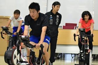 ジャパン・ライジング・スター・プロジェクトの最終選考で自転車をこぐ参加者(11月3日、東京都世田谷区)