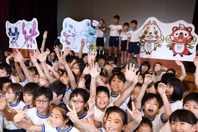 2020年東京五輪・パラリンピックのマスコット最終候補3作品と写真に納まる児童(12月7日午前、東京都渋谷区)