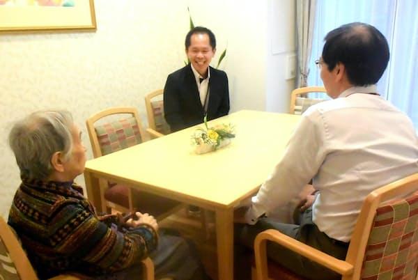 まどか深大寺の多目的室で、入居した母親と歓談するAさん(右)とホーム長(東京都調布市)