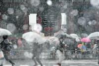雪が降るなか浅草寺の雷門前を歩く人たち(22日午後、東京都台東区)