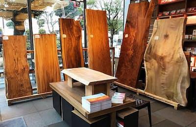 代官山蔦屋書店1号館の1階の人文コーナーを一番奥まで進むと、大きな一枚板が6枚置かれている異空間が現れる。なぜ、書店に一枚板が売られているのだろうか(日経トレンディネットより)