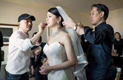 吉川康雄さん(左)が仕上げた花嫁メークは自然体だ(大阪市)