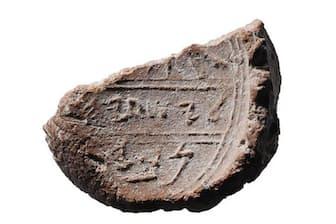 粘土に押され、一部が欠けた2700年前の封印。古代エルサレムのごみ捨て場から出土した。刻まれているのは、聖書に登場する預言者イザヤの名かもしれない。(PHOTOGRAPH BY OURIA TADMOR/ EILAT MAZAR)