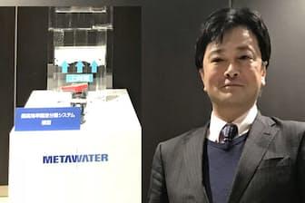 メタウォーターの大西正浩氏と高速ろか機(モデル)