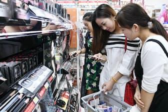 外国人旅行客にとってスマホは貴重な情報ツールだ(東京都台東区のドラッグストア)