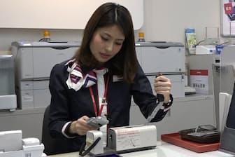 店員が携帯電話に針を貫通させ、個人情報を消す(東京・品川のドコモショップ五反田店)