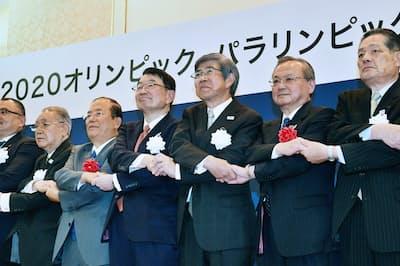 東京五輪・パラリンピック警備の共同企業体を設立し、記念写真に納まるセコムの中山社長(右から4人目)、綜合警備保障の青山社長(同3人目)ら(東京都千代田区)