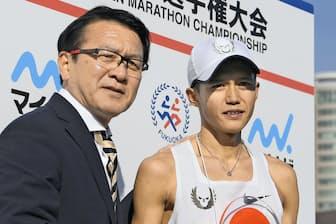 福岡国際マラソンのレース後、瀬古利彦さん(左)と握手する大迫傑選手(福岡市の平和台陸上競技場)=共同