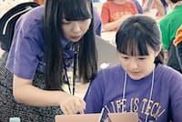 指導役の大学生と一緒にスマホアプリの開発に取り組む中学生(東京・世田谷)