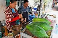 未熟なパパイアを棒でたたき、調味料などと混ぜる(バンコク中心部の屋台)=柏原敬樹撮影