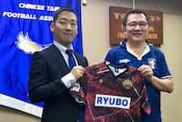 パートナーシップ協定を結びFC琉球のユニフォームを手にする倉林啓士郎社長(左)と台湾サッカー協会の林振義会長(2017年9月、台湾サッカー協会)=FC琉球提供