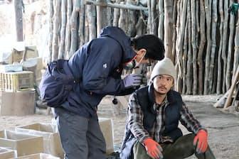 炭焼き小屋で稲垣吾郎(右)に炭をたたき、音を聴く演技をつける阪本監督