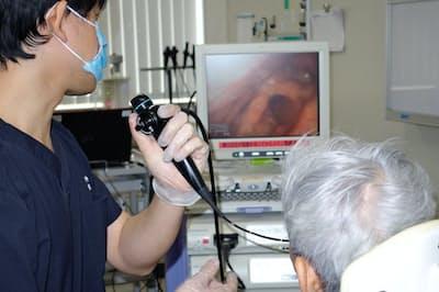 患者の鼻から入れた内視鏡でのどの動きをモニターに映しながら飲み込むコツを伝える浦長瀬医師(神戸市の神鋼記念病院)