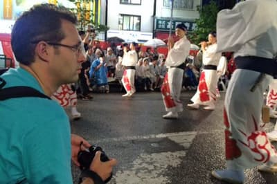 「ジャパンガイド」は外国人記者がユーザーの立場で記事を書いている(写真は東京・高円寺の阿波おどりを取材するステファン・シャウエッカー編集長)