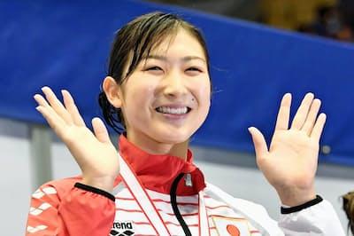 競泳ジャパンOP女子100メートル自由形で優勝し、表彰台で笑顔の池江璃花子(5月、東京辰巳国際水泳場)=共同