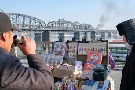 丹東の中朝友誼橋付近にある土産物店で品物を物色する男性。この橋は朝鮮戦争中に米軍の爆撃を受けた後、再建されたものだが、壊れた橋の一部は現在、戦争記念碑になっている(PHOTOGRAPH BY ELIJAH HURWITZ)