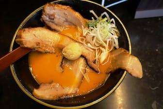 「豚骨スープ・スパイシーガーリック味」(950円)に「豚チャーシュー」(150円)をトッピング。チャーシューはどんぶりからはみだす大きさ