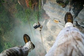 宙吊りになった写真家レナン・オズターク氏の足。ハチに刺されないようテープを巻いている。その下で縄ばしごを登るのはクルン族最後の蜂蜜採りマウリさん(PHOTOGRAPH BY RENAN OZTURK)