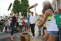 地元の人たちの歓迎を受け、餅つきを体験するブルガリアの新体操選手(山形県村山市)