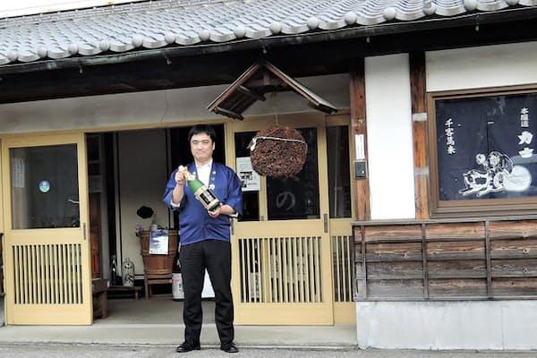 創業270周年を迎えた釜屋 金賞受賞酒を手に立つ小森順一社長