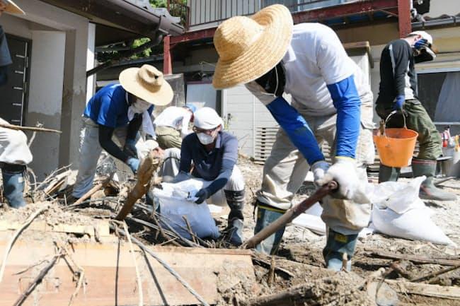強い日差しを受けながら、住宅の片付けをする人たち(15日午前、広島県坂町)