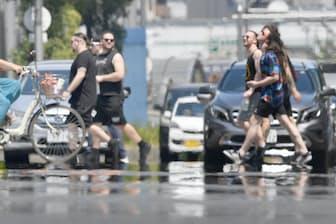 逃げ水やかげろうが立つ道路を歩く外国人観光客(7月23日、大阪市中央区)