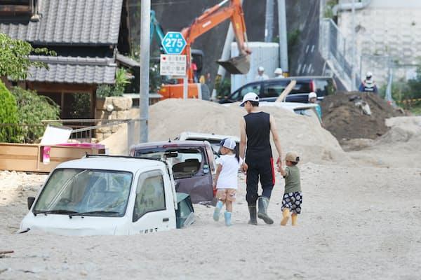 土砂に覆われた住宅地を歩く住民(7月13日、広島県坂町)