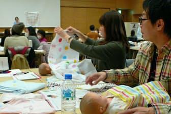 出産前の夫婦を対象にしたセミナーで乳児の世話の仕方を学ぶ男性(右)