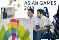アジア大会の公開競技「eスポーツ」のサッカーゲーム決勝でイランと対戦する杉村直紀選手(左)と相原翼選手(9月1日、ジャカルタ)=共同