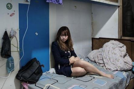 中国、北京の魏公村地区にあるノン・イン核シェルターの自室で、ベッドに座るシェンさん(23)。多くの若者がより豊かな生活を求め、地方を後にして北京に移住している(PHOTOGRAPH BY ANTONIO FACCILONGO)